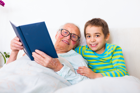 grand child: happy boy laying in bed with her grandmother who is reading a book with farytales.