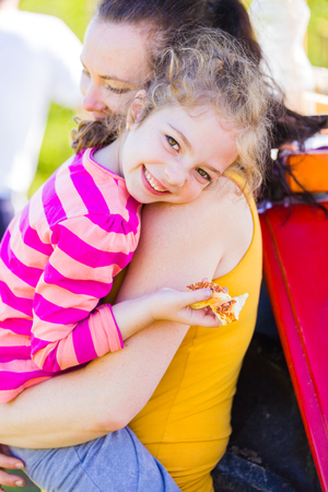 Mother and daughter hugging each other, bonding in a warm summer day. Stock Photo