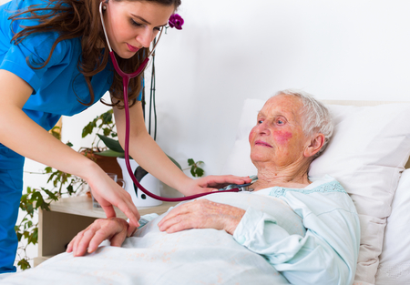 geriatrician: Young geriatrician doctor listening to the lung and hearth sounds of a senior patient.
