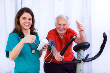 Elderly woman doing sport effort on a spinning bike having hear hart rate and blood pressure monitored. Archivio Fotografico