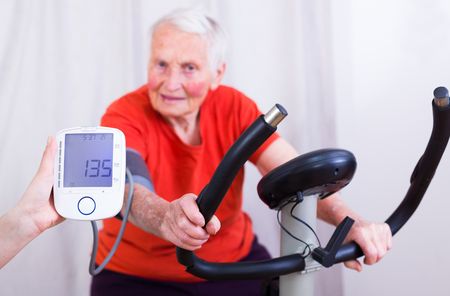 blood sport: Elderly woman doing sport effort on a spinning bike having hear hart rate and blood pressure monitored. Stock Photo