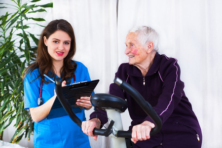geriatrician: Elderly woman doing sport effort while a kind geriatrician doctor is attending the event in a nursing home.