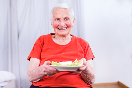 plateful: Old woman having a healty meal in the nursing home, a plateful of fruits. Stock Photo