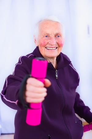 weak: Elderly woman training her body, not letting herself get weak.