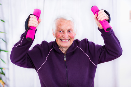 disease patients: Senior woman training, doing fitness with pink weights at home.
