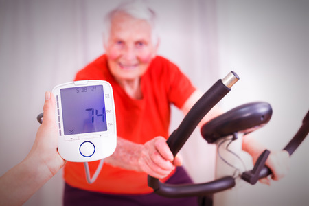 stationary: Elderly woman training, making effort, having hear heart condition, rate and blood pressure monitored by geriatric doctor.