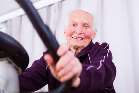stationary bike: Senior woman on stationary bike indoors in a nursing home.