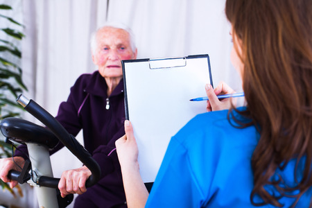 pacientes: médico geriátrico tomar notas sobre el estado gealth de una mujer mayor haciendo deporte en un hogar de ancianos.