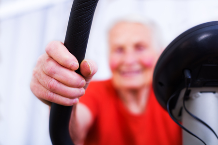 infirm: Close-up of an elderly womans hands doing sport, training on a stationary bicycle indoors in the nursing home.