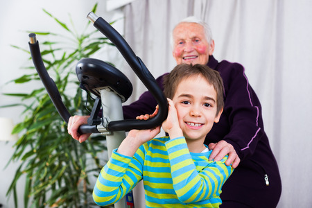 stationary bike: Grandmother training on stationary bike in the company of her grandson.