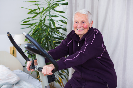 Senior woman on stationary bike indoors in a nursing home.