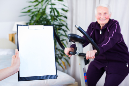 geriatrician: Geriatrician taking notes about the effort capacity of an elderly woman in a nursing home. Stock Photo