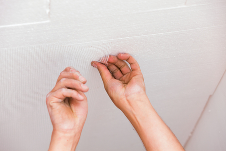 skim: Construction worker aplying glass fiber net to ceiling before skim coating the sourface.