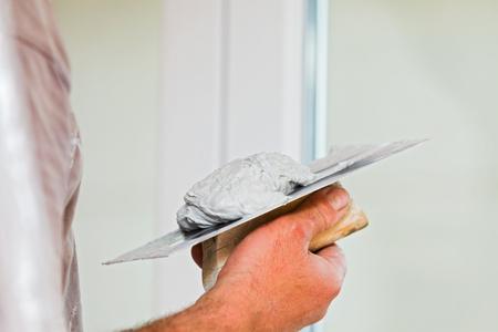 skim: Construction worker using skim coating material on steel trowel.