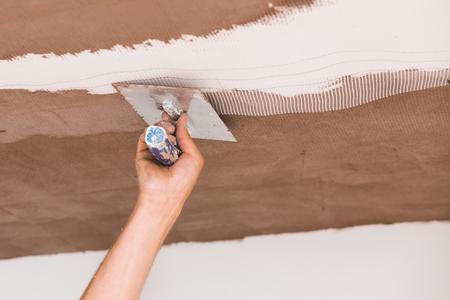 fiberglass: Construcción trabajador descremada recubrir el techo después de la aplicación de la red de fibra de vidrio. Foto de archivo
