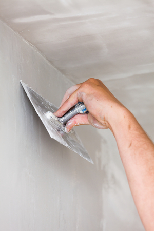 smoothing: Construction worker holding plastering trowel, smoothing wall defects. Stock Photo