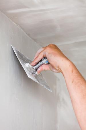 Travailleur de la construction exploitation plâtrage truelle, lisser les défauts du mur.