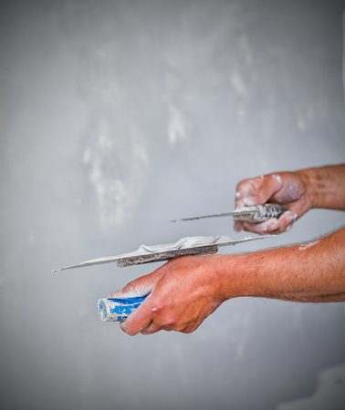 skim: Professional construction worker applying skim coating material to the freshly made plasterboard wall before painting.