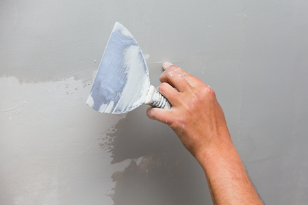 drywall: Construction worker holding a trowel against unfinished drywall.