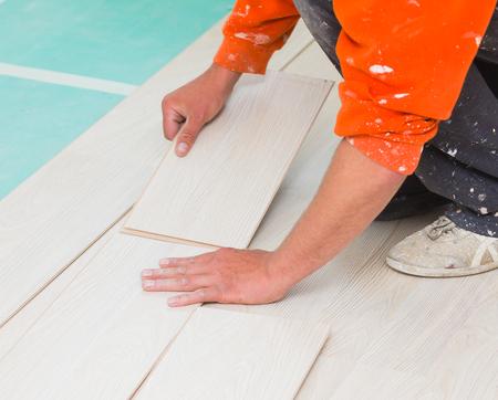 lining: Handyman laying down laminate flooring boards while renovating a house.