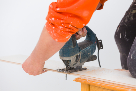 electric saw: Handyman cutting laminate floor board with electric saw to fit the given situation. Stock Photo