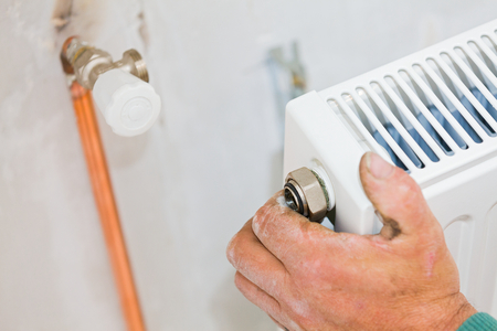 home heating: Handyman mounting radiator to fix home heating system. Stock Photo