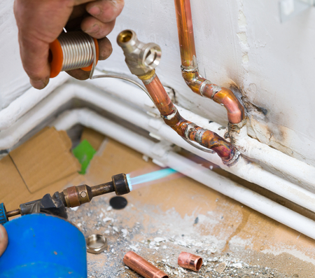 splice: Handyman soldering copper tubes together for home radiators and heating system. Stock Photo