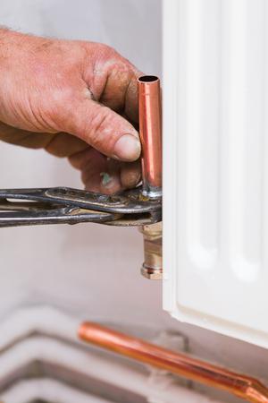 mounting: Handyman mounting copper conduit on home radiator. Stock Photo