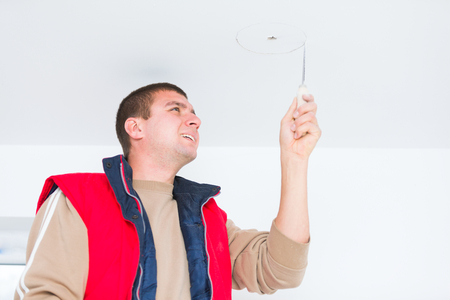 mounting: Electrician working with hanging cords on the wall, mounting light.