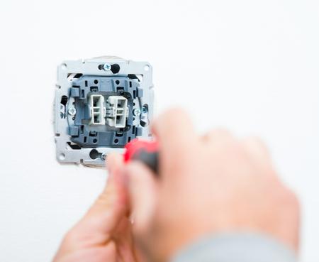 enchufe de luz: manos Electrcian la instalación de enchufe de la luz en la pared.