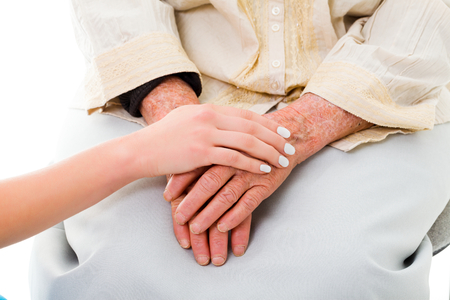 caring hands: Old worryed woman conforted by a younger relative.