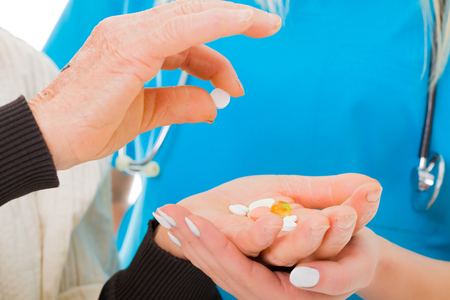 infirm: Elderly woman picking one pill from her hands full with medications. Stock Photo