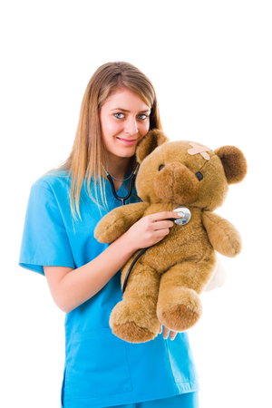 Beautiful young pediatrician presenting medical procedure with the help of a teddy bear in a fun way. photo