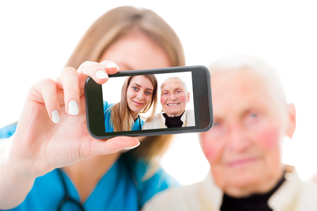 Young doctor taking a selfie with the elderly grandmother in the residential care home to send to the family. photo