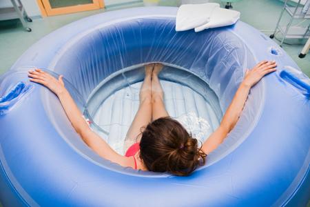 empezar: Joven mujer embarazada durante el parto en el hospital se sienta en una piscina de agua. Foto de archivo