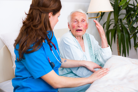 Geriatric doctor listening to the elderly woman patient with attention and care.