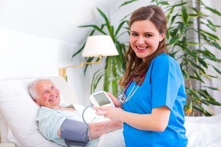 Kind geriatric doctor measuring the blood pressure and heart rate of happy elderly patient.