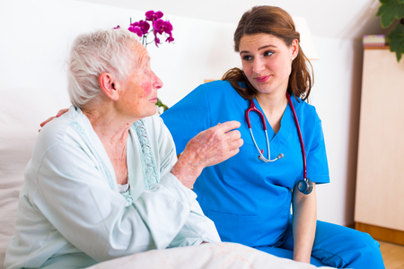geriatrician: Geriatric doctor and elderly woman patient talking in the nursing home, spending time. Stock Photo