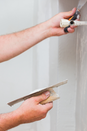 defects: Construction worker holding plastering trowel, smoothing wall defects. Stock Photo