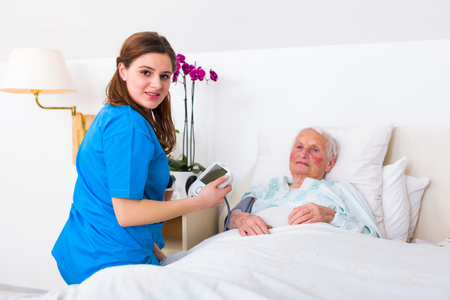 Happy senior woman having her blood pressure measured in bed in a nursing home by her caregiver.