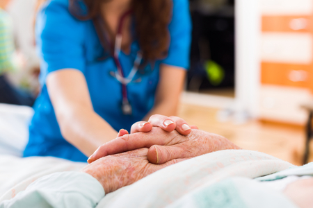 Senior woman in the nursing home getting support from a younger person. Stock Photo