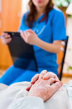Senior patients hands folded in bed in residential care home and a nurse in the background examining the patient. Stock Photo