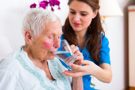 Kind caregiver bringing water to the thirsty sick elderly woman in bed. Stock Photo