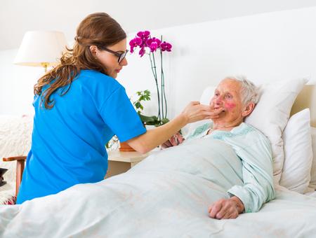 Zorgzame verpleegster het verzorgen van een droge huid een senior vrouw in de norsing huis.