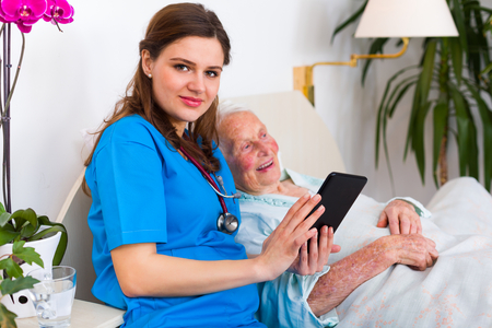 health technology: Caring nurse showing a digital tablet to an elderly woman in a nursing home.