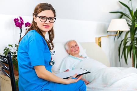 Beautiful nurse visiting an elderly woman patient in the nursing home, registering her health status.