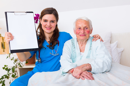 Oncologist doctor showing a blank register to the camera with a senior woman who got well from illness. Archivio Fotografico