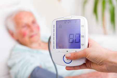 Caregiver measuring elderly womans diastolic blood pressure in hospital. Stock Photo