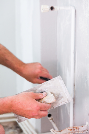 construction material: Professional construction worker applying skim coating material to the freshly made plasterboard wall before painting.