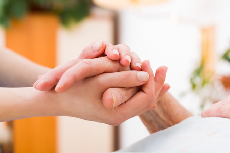 incapacity: Nurse holding the hand of an elderly woman, showing sympathy and kindness.